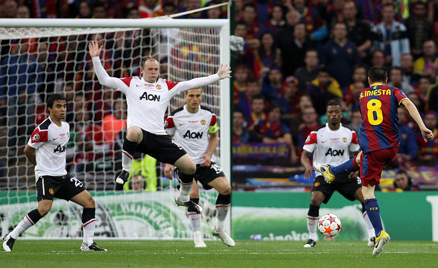 Wayne Rooney attempts to block a shot from Andres Iniesta