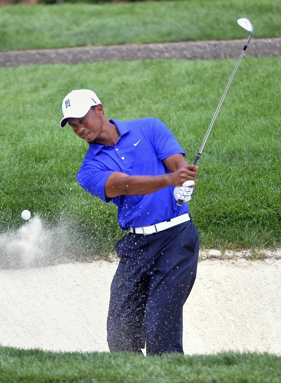 Tiger Woods plays from a bunker during practice