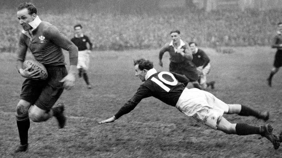 Wales' Wilf Wooller dodges a tackle from Scotland's John Craig